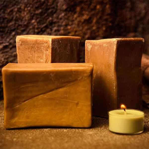 Alleppo Seife neben einer Kerze und vor einer dunklen Wand