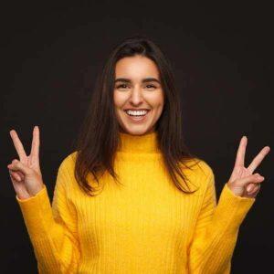 Frau mit gelbem Pullover zeigt Victory Zeichen