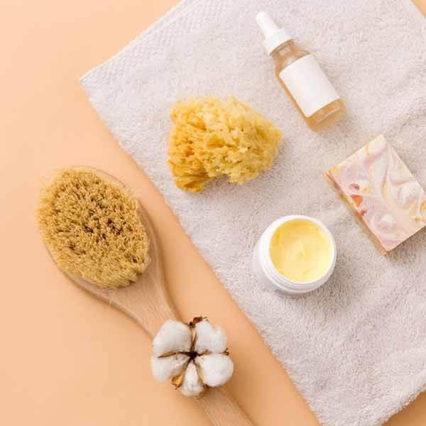 Naturschwamm für die Gesichtspflege liegt auf Handtuch neben einer Badebürste