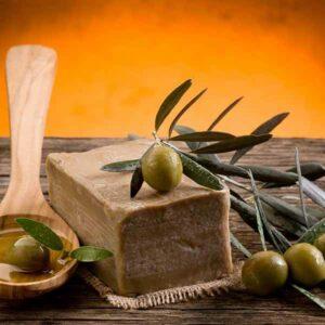 Stück Aleppo Seife mit Oliven auf einem Holztisch