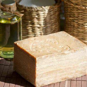 Duschbrocken aus Aleppo liegt auf einem Holztisch neben einer Flasche mit Olivenöl
