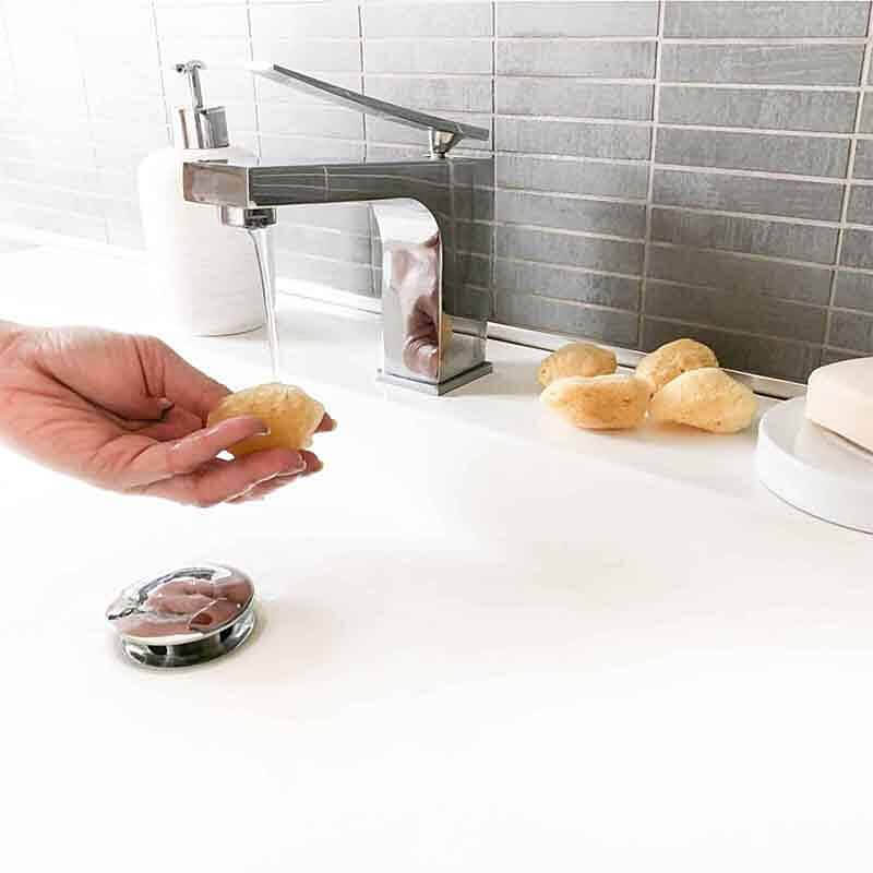 Eine Frauenhand reinigt Menstruationsschwämmchen unter Wasser