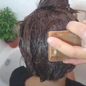Aleppo Seife schäumt nasse Haare ein, dahinter eine Badewanne