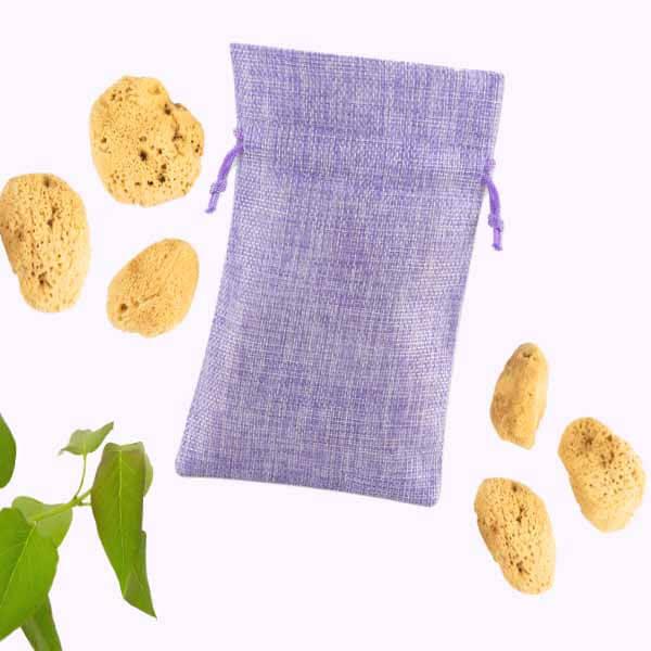 Fünf Menstruationsschwämmchen liegen neben einem lila Jutebeutel