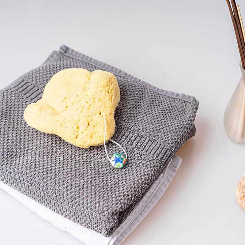 Gelber Naturschwamm mit Kordel liegt auf einem Handtuch